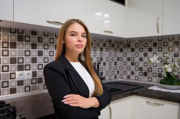 Jovem e fofa designer feminina no interior luxuoso da cozinha branca e moderna com design clean