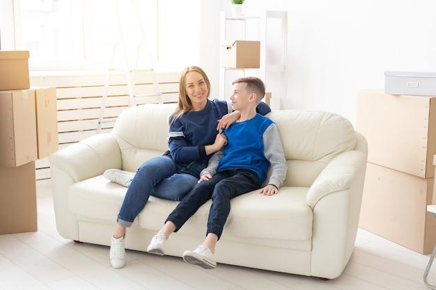 Jovem e fofa mãe solteira e filho estão felizes com a mudança para a nova casa. conceito de inauguração de casa e extensões do espaço familiar.