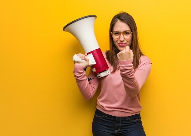 Jovem e fofa segurando um megafone, mostrando o punho para a frente, expressão de raiva