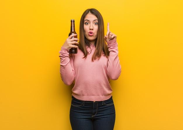 Jovem e fofa segurando uma cerveja, tendo uma ótima ideia, o conceito de criatividade