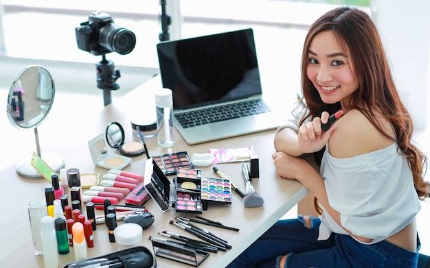 Jovem e fofa vlogger, influenciadora ou vendedora on-line asiática sentada com produtos cosméticos e uma câmera dslr e um laptop pronto para transmitir uma transmissão ao vivo on-line ou gravar um vídeo.