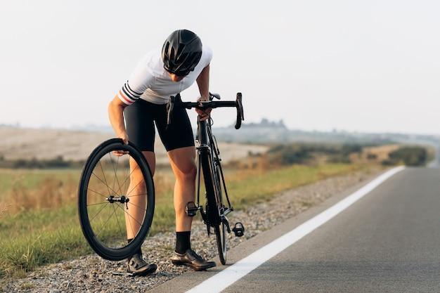 Jovem e forte ciclista em roupas esportivas e consertando o capacete da roda da bicicleta preta em pé na estrada pavimentada