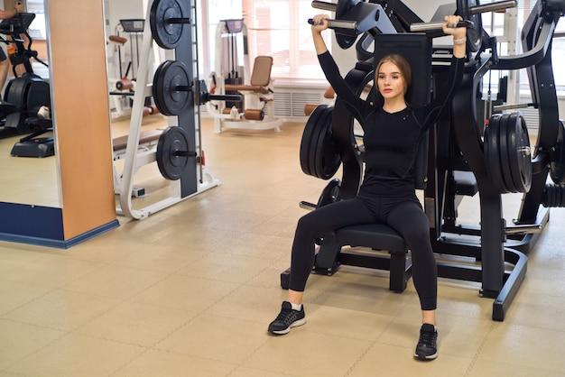 Jovem e forte desportista fazendo exercícios de levantamento do ombro na máquina de ginástica