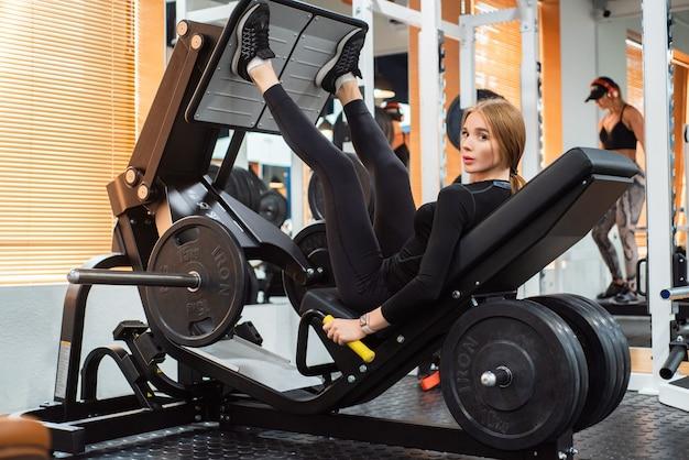 Jovem e forte desportista fazendo exercícios de perna na máquina de ginástica