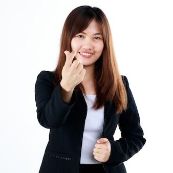 Jovem e fresco graduado olhar empresária asiática em pose de terno em gesto de publicidade, mostrar os dedos em sinal de coração para aceitar ou amar algo. isolado em um fundo branco.