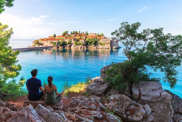 Jovem e garota meditam na rocha em frente a sveti stefan islland na riviera de budva, montenegro.