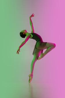 Jovem e graciosa dançarina de balé isolada no fundo gradiente rosa-esverdeado do estúdio