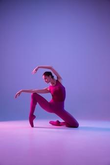 Jovem e graciosa dançarina de balé isolada no fundo roxo do estúdio em luz de néon