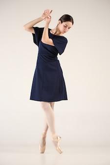 Jovem e incrivelmente linda bailarina está dançando em um estúdio azul