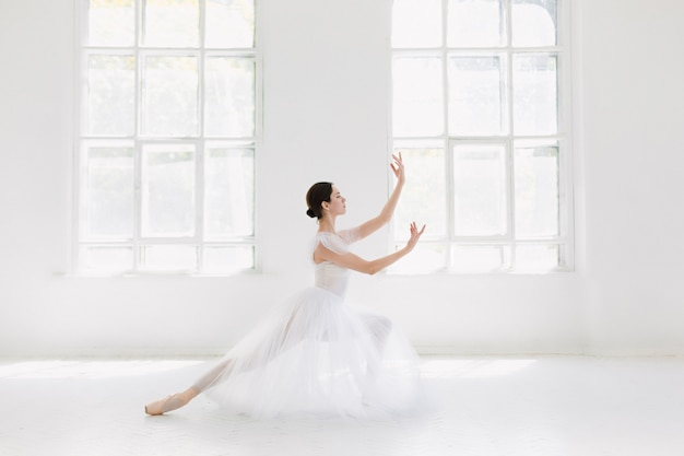 Jovem e incrivelmente linda bailarina está posando e dançando em um estúdio branco