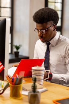 Jovem e inteligente trabalhador de escritório olhando os documentos enquanto faz seu trabalho