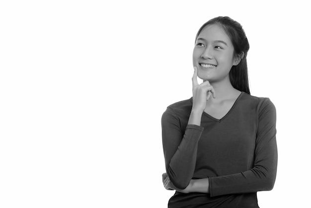 Jovem e linda adolescente asiática isolada contra uma parede branca em preto e branco