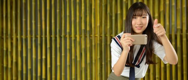Jovem e linda adolescente asiática tirando foto com o telefone contra a cerca de bambu