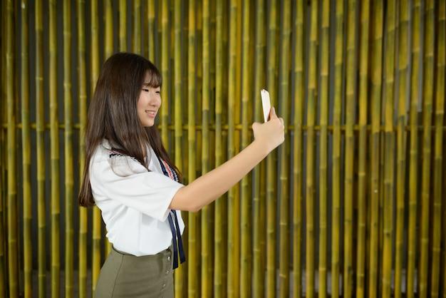 Jovem e linda adolescente asiática tirando uma selfie contra a cerca de bambu