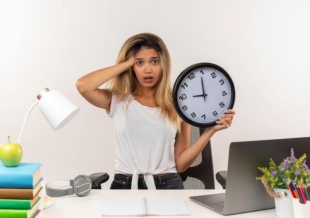 Jovem e linda aluna impressionada atrás de uma mesa com ferramentas escolares, colocando a mão na cabeça e segurando um relógio isolado no branco