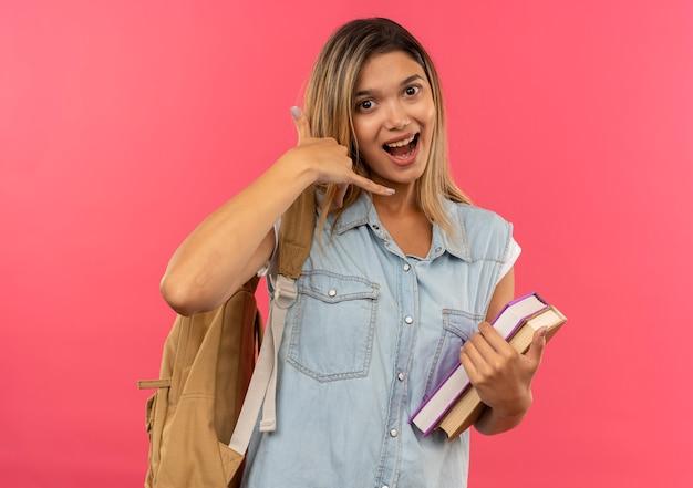 Jovem e linda aluna impressionada com uma bolsa nas costas, segurando livros e fazendo sinal de chamada isolado em rosa