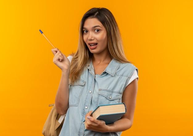 Jovem e linda aluna impressionada com uma bolsa nas costas, segurando um livro e uma caneta isolados em laranja