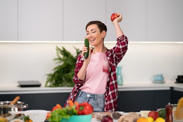 Jovem e linda dona de casa com um penteado bob, cozinhando o jantar ou o almoço em pé na cozinha