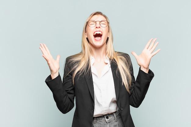 Jovem e linda empresária gritando furiosamente, sentindo-se estressada e irritada com as mãos para o alto, dizendo por que eu