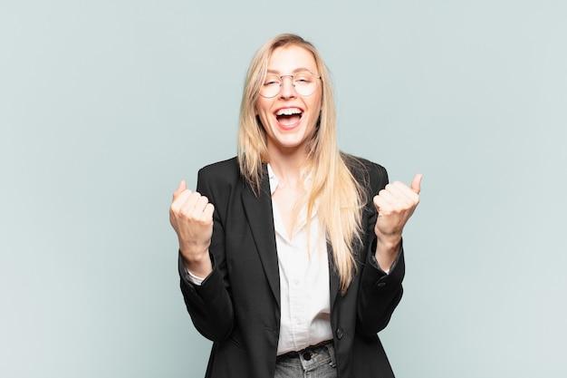 Jovem e linda empresária gritando triunfantemente, rindo e se sentindo feliz e animada enquanto festeja o sucesso
