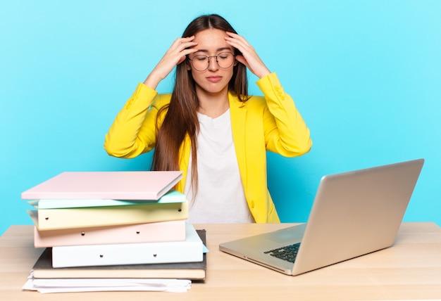 Jovem e linda empresária parecendo concentrada, pensativa e inspirada, fazendo um brainstorming e imaginando com as mãos na testa