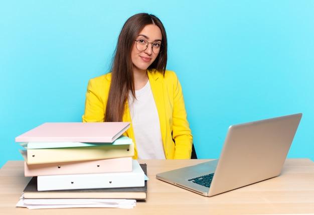 Jovem e linda empresária parecendo orgulhosa, confiante, descolada, atrevida e arrogante, sorrindo e se sentindo bem-sucedida