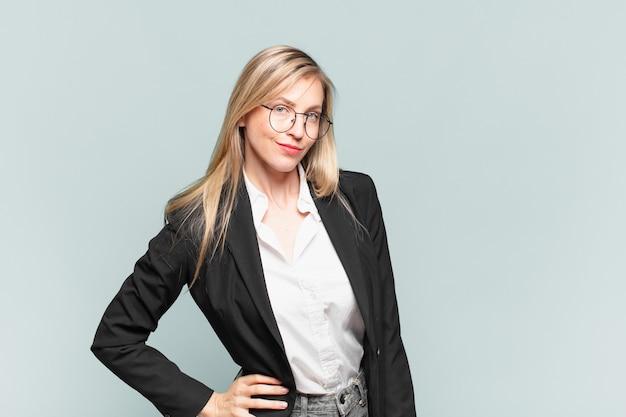 Jovem e linda empresária parecendo orgulhosa, confiante, descolada, atrevida e arrogante, sorrindo, sentindo-se bem-sucedida