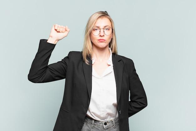 Jovem e linda empresária se sentindo séria, forte e rebelde, levantando o punho, protestando ou lutando pela revolução