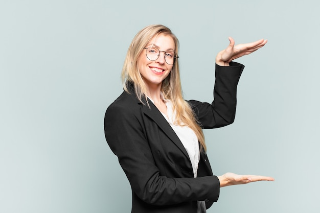 Jovem e linda empresária segurando um objeto com as duas mãos no espaço ao lado, mostrando, oferecendo ou anunciando um objeto