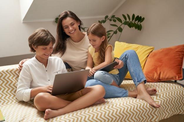 Jovem e linda família caucasiana mãe e seus dois lindos filhos relaxando no sofá assistindo
