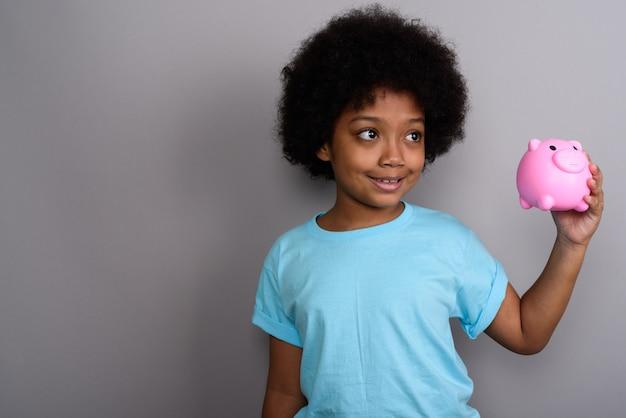 Jovem e linda garota africana contra uma parede cinza