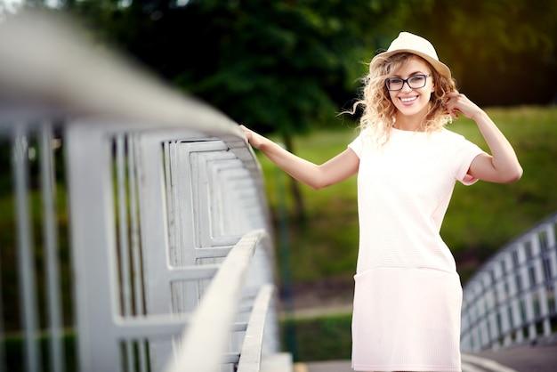 Jovem e linda garota alegre de chapéu e óculos, andando na cidade de verão e sorri
