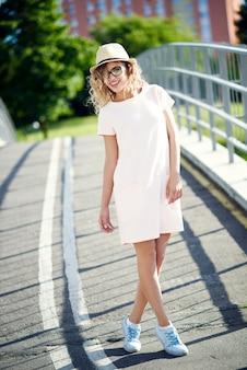 Jovem e linda garota alegre de chapéu e óculos, andando na cidade de verão e sorrisos
