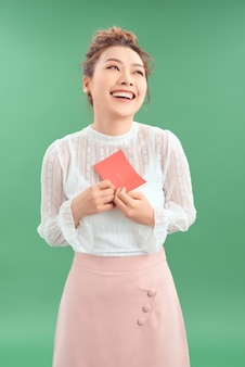 Jovem e linda garota asiática feliz com um cartão postal de dia dos namorados amoroso sobre fundo verde
