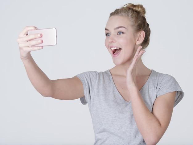 Jovem e linda garota caucasiana faz selfies. mulher feliz e maravilhosa com o celular nas mãos