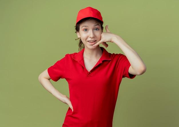 Jovem e linda garota de entrega impressionada de uniforme vermelho e boné, colocando a mão na cintura e fazendo um gesto de chamada, isolado em um fundo verde oliva com espaço de cópia