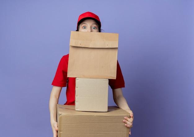 Jovem e linda garota de entrega impressionada usando uniforme vermelho e boné segurando caixas de papelão e um pacote de papel e olhando por trás do pacote de papel