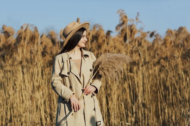 Jovem e linda garota elegante com um casaco bege e um chapéu entre juncos fofos e secos em um dia quente e ensolarado de primavera
