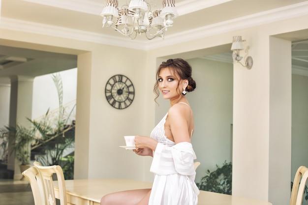 Jovem e linda garota feliz de luxo em cueca branca e camisola bebendo café da manhã