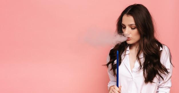 Jovem e linda garota fuma narguilé, shisha. produz fumaça em sua boca. o prazer de fumar. lugar para o seu texto.