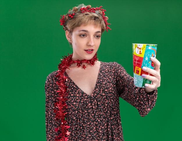 Jovem e linda garota impressionada usando coroa de flores de natal e guirlanda de ouropel em volta do pescoço esticando o copo de plástico de natal em direção à câmera, olhando para ele isolado no fundo verde