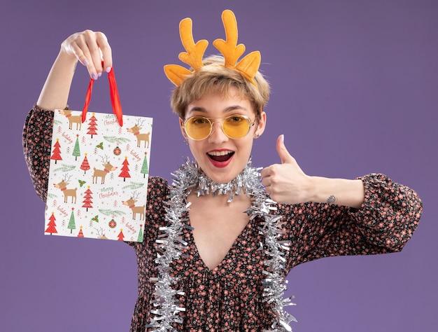 Jovem e linda garota impressionada usando uma bandana de chifres de rena e uma guirlanda de ouropel no pescoço, com óculos segurando uma sacola de presente de natal, olhando para a câmera mostrando o polegar isolado no fundo roxo