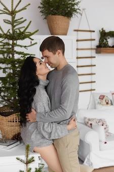 Jovem e linda garota modelo em suéteres aconchegantes se abraçando no interior decorado para o natal