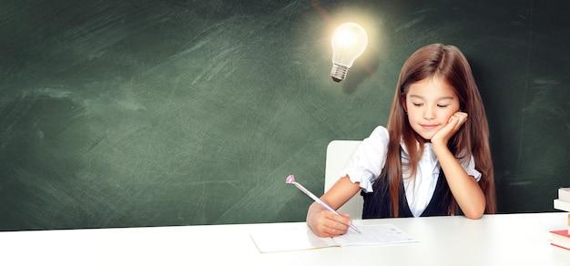 Jovem e linda garota na lousa com uma lâmpada na cabeça