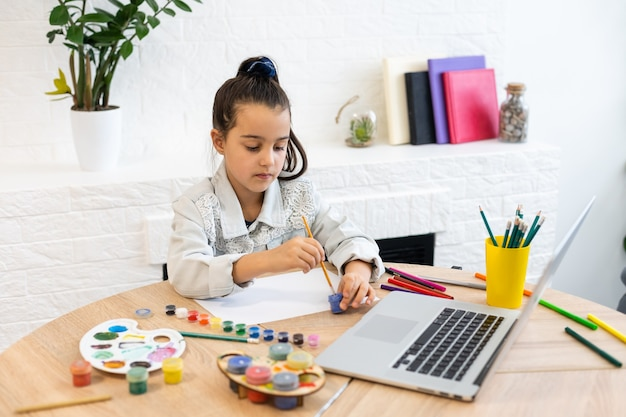 Jovem e linda garota passando um tempo desenhando usando aulas on-line no laptop educação on-line de ensino à distância.