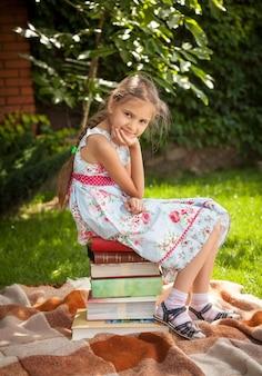 Jovem e linda garota sentada em uma grande pilha de livros no jardim