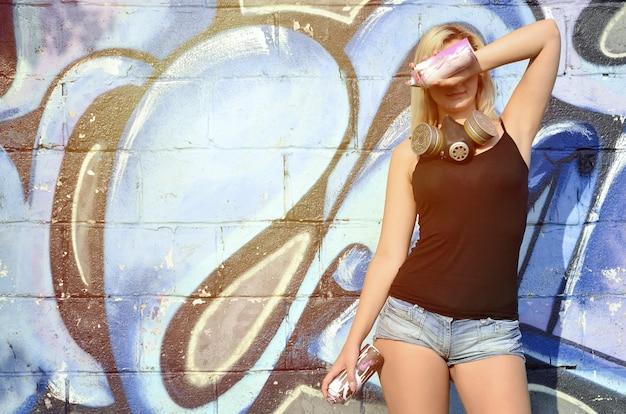 Jovem e linda garota sexy sorridente grafiteiro com máscara de gás