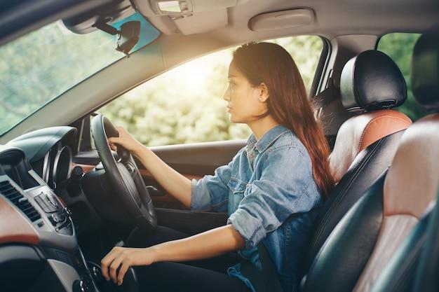 Jovem e linda garota sorridente dirigindo um carro