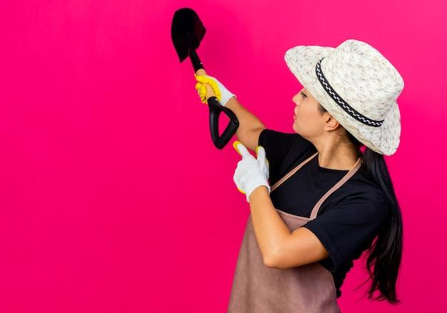 Jovem e linda jardineira com luvas de borracha, avental e chapéu segurando uma pá apontando com os dedos para trás em pé sobre a parede rosa