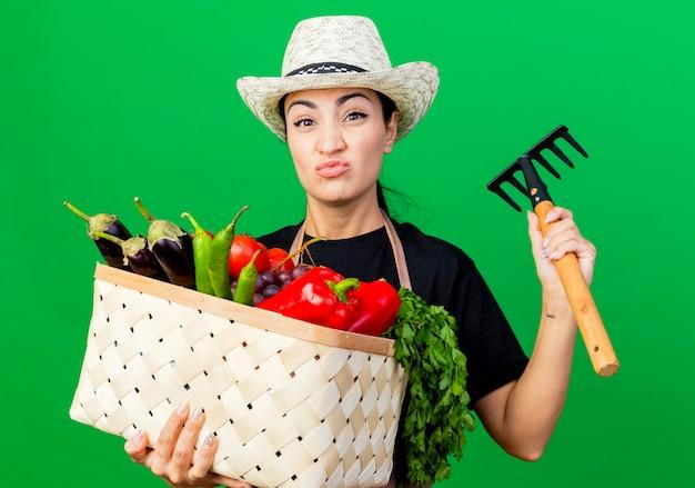 Jovem e linda jardineira de avental e chapéu segurando uma cesta cheia de legumes e um mini ancinho olhando para a frente e ficando descontente em pé sobre a parede verde